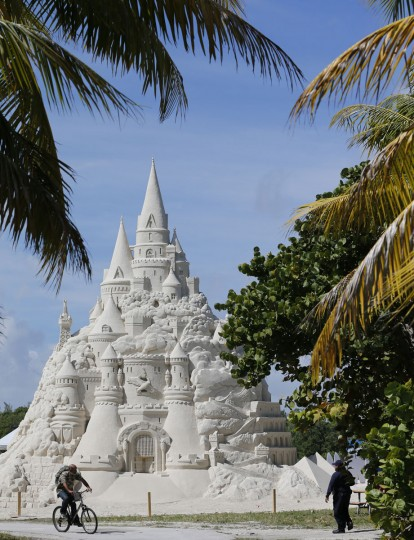 A cyclist rides past a sandcastle built for a record attempt for the tallest sandcastle, Monday, Oct. 26, 2015, on Virginia Key Beach in Miami. The castle was commissioned by Turkish Airlines to highlight their new nonstop service from Miami to Istanbul. (AP Photo/Wilfredo Lee)