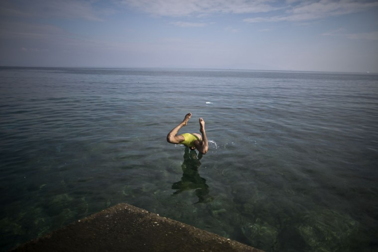 An Afghan refugee jumps into the sea at the port of Mitylene on the northeast Greek island of Lesbos while waiting to get on board a ferry traveling to Athens, Thursday, Oct. 8 , 2015. More than 500,000 people have arrived in the European Union this year, seeking sanctuary or jobs and sparking the EU's biggest refugee emergency in decades. (AP Photo/Muhammed Muheisen)