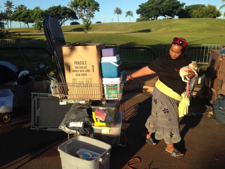 Loveleen Mori, 27, a homeless woman living in a large encampment in the Kakaako neighborhood of Honolulu, holds her dog as she tries to figure out where to bring her belongings as city officials start to sweep the camp, Thursday, Oct. 8, 2015. Honolulu city crews are clearing a major chunk of the encampment that once was home to hundreds of people. (AP Photo/Cathy Bussewitz)