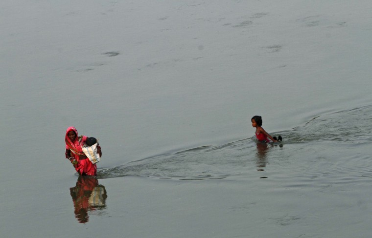 A village woman followed by a child crosses the River Daya to get to the other side of the bank on the outskirts of the eastern Indian city of Bhubaneswar, India, Friday, Oct. 9, 2015. The nearest bridge across the river being some distance away, villagers opt to wade across the river to get to their village when the water levels are low. (AP Photo/Biswaranjan Rout)