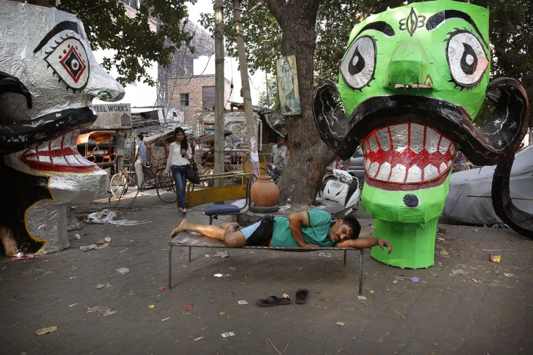An Indian artist rests on a cot after preparing effigies of the ten-headed demon god Ravana in preparation for the upcoming Dessehra festival in New Delhi, India, Tuesday, Oct. 20, 2015. Dussehra, also known as Vijayadashami, commemorates the victory of the Hindu god Rama over Ravana, an evil ruler who had abducted Rama's wife, Sita Devi. Rama killed Ravana to free Sita. The burning of effigies of Ravana, signifying the victory of good over evil, bring the festivities to a close. (AP Photo/Manish Swarup)