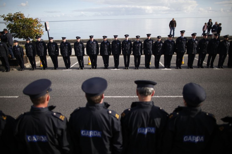 Thousands of police line the main street for the funeral of Irish policeman Tony Golden in Blackrock Ireland, Thursday, Oct. 15, 2015. Ireland's leaders and thousands of police are attending a state funeral for an officer shot to death by an Irish Republican Army suspect free on bail, a killing that has raised questions about arming police and toughening bail rules. (AP Photo/Peter Morrison)