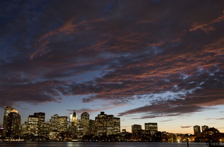 The sunset illuminates clouds over Boston harbor and the city skyline Monday, Oct. 5, 2015 in Boston. (AP Photo/Michael Dwyer)
