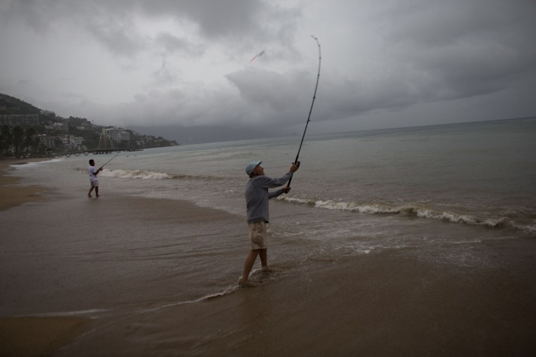 Mike Anderson of Minnesota, right, fishes alongside his friend and local fisherman Miguel Pilas during a steady rain as Hurricane Patricia approaches Puerto Vallarta, Mexico, Friday, Oct. 23, 2015. Hurricane Patricia barreled toward southwestern Mexico Friday as a monster Category 5 storm, the strongest ever in the Western Hemisphere. (AP Photo/Rebecca Blackwell)
