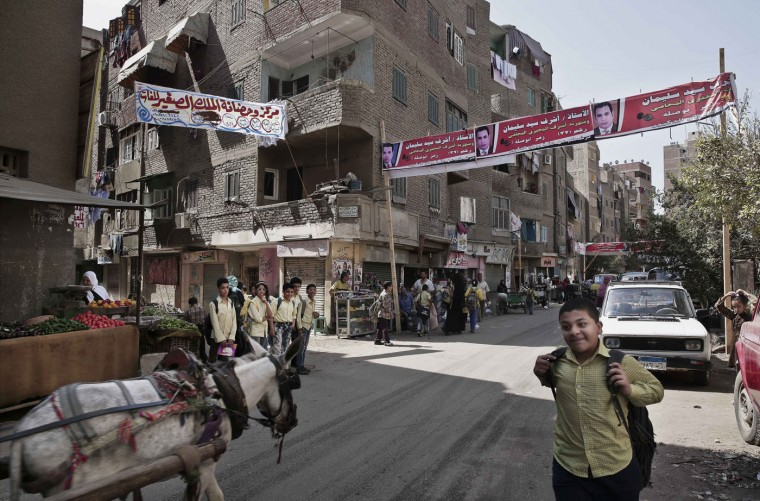 "Egyptian school children make their way home after school in front of a banner with the photo of a parliamentary candidate, and Arabic that reads, ""Ashraf Sayed Soliman, your candidate in the Boulaq El Dakrour cycle,"" on a street in Boulaq El Dakrour district of Giza, near Cairo, Egypt, Thursday, Oct. 8, 2015. Egypt's long-awaited parliamentary elections will start on Oct. 18-19, a hoped-for step toward democracy amid a harsh crackdown on dissent. The second stage of the staggered vote will take place on Nov. 22-23. Final results will be announced in early December. (AP Photo/Nariman El-Mofty)"