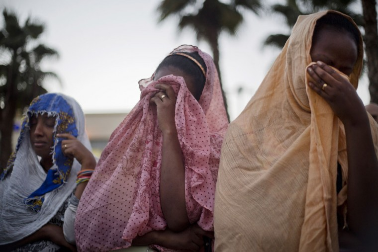 Eritrean migrants women mourn during a memorial gathering for Habtom Zerhom, in Tel Aviv, Israel, Wednesday, Oct. 21, 2015. Zarhum died of his wounds after an Israeli security guard fired at him and later was beaten by a mob that mistakenly believed he was a Palestinian attacker during a shooting in the southern city of Beersheba on Sunday. Israeli security officials said a 21-year-old Arab Israeli carried out the attack, killing an Israeli soldier and wounding 10 people. (AP Photo/Ariel Schalit)