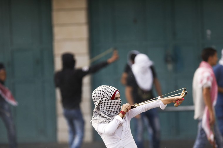 A Palestinian woman uses a slingshot during clashes with Israeli troops in the West Bank city of Bethlehem on Tuesday, Oct. 13, 2015. A pair of Palestinian men boarded a bus in Jerusalem and began shooting and stabbing passengers, while another assailant rammed a car into a bus station before stabbing bystanders, in near-simultaneous attacks Tuesday that escalated a monthlong wave of violence. (AP Photo/Nasser Shiyoukhi)