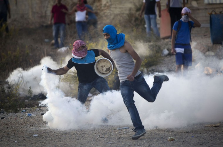A Palestinian protester throws back a tear gas canister that was fired by Israeli troops during clashes near Ramallah, West Bank, Thursday, Oct. 15, 2015. In the current wave of violence, eight Israelis have been killed in stabbing and shooting attacks, as of Thursday. Thirty-one Palestinians have been killed, including 14 identified by Israel as attackers, and the others in clashes between stone-throwers and Israeli troops. (AP Photo/Majdi Mohammed)
