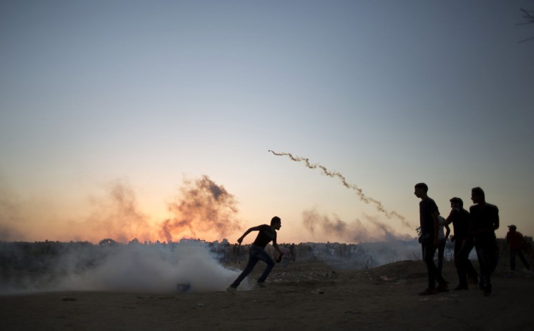 Palestinian protesters run for cover from tear gas fired by Israeli soldiers during clashes on the Israeli border with Gaza in Buriej, central Gaza Strip, Thursday, Oct. 15, 2015. (AP Photo/ Khalil Hamra)