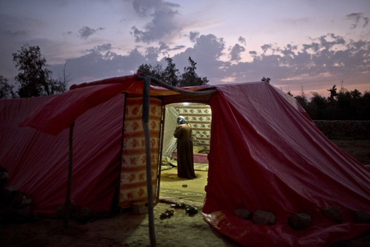 Syrian refugee Ghaziyya Alsaad, 58, offers evening prayers, known as Maghrib, inside a tent at an informal tented settlement near the Syrian border on the outskirts of Mafraq, Jordan, Tuesday, Oct. 20, 2015. (AP Photo/Muhammed Muheisen)