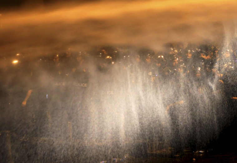 Lebanese riot policemen are seen through the spray of water cannons used against anti-government protesters against the ongoing trash crisis and government corruption, in downtown Beirut, Lebanon, Thursday, Oct. 8, 2015. Lebanese security forces used water cannons and eventually fired tear gas canisters to disperse dozens of anti-government protesters who tried to get past security barricades and reach parliament. (AP Photo/Hussein Malla)