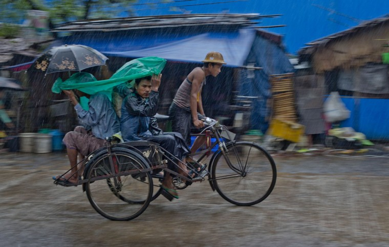 Men travel in a rickshaw in rain in Hlaing Tharyar, suburbs of Yangon, Myanmar, Tuesday, Oct. 6, 2015. Downpours during the monsoon season are intense, and often more than 100 millimeters (3.9 inches) of rain falls in an hour resulting in flash floods and traffic jams. (AP Photo/Gemunu Amarasinghe)