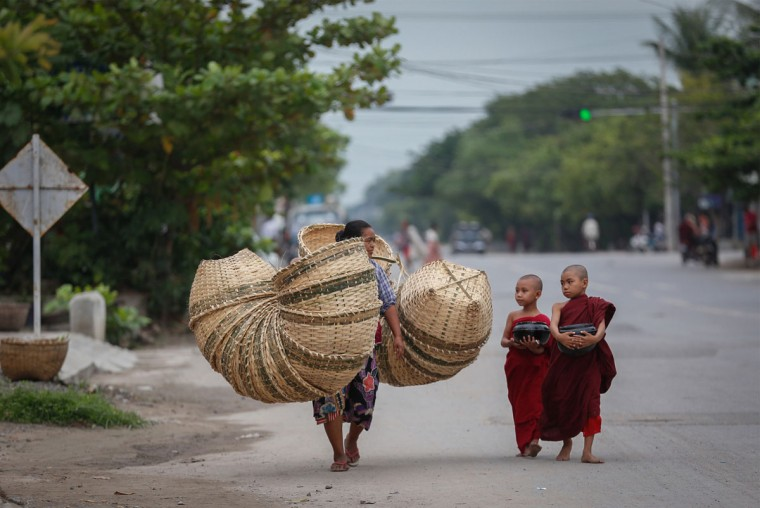 Two novice Buddhist monks walk alongside a basket seller to collect alms following a clerics rule of no footwear nor use of umbrellas in Mandalay, Myanmar, Friday, Oct. 9, 2015. (AP Photo/Hkun Lat)