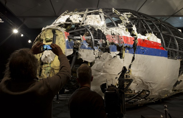 Journalists take images of part of the reconstructed forward section of the fuselage after the presentation of the Dutch Safety Board's final report into what caused Malaysia Airlines Flight 17 to break up high over Eastern Ukraine last year, killing all 298 people on board, during a press conference in Gilze-Rijen, central Netherlands, Tuesday, Oct. 13, 2015. (AP Photo/Peter Dejong)