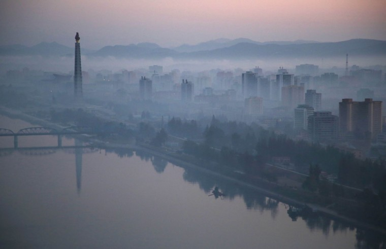 Dawn breaks over Pyongyang, North Korea, as buildings poke through the midst and the Juche Tower, left, stands by the Taedong riverbank on Tuesday, Oct. 13, 2015. (AP Photo/Wong Maye-E)