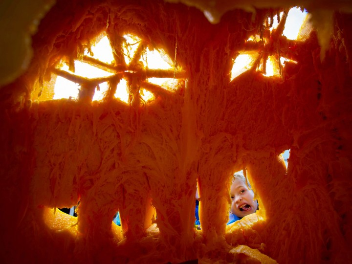 Kyle McDowell, a kindergarten student at O'Hara Catholic School, emulates the face of a Jack O'Lantern created from a 800 pound pumpkin by carver Scott Cully in Eugene, Ore., according to the Register-Guard on Thursday, Oct. 22, 2015. (Andy Nelson/The Register-Guard via AP)