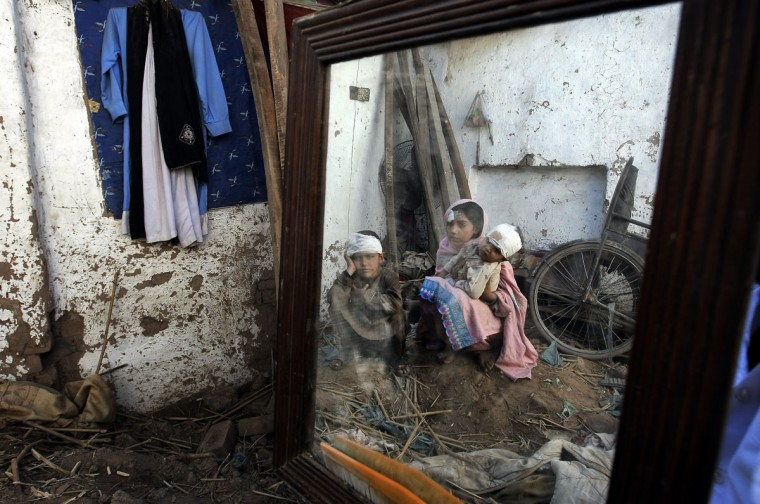 Pakistani children reflected in a mirror sit on the ground in their home damaged from an earthquake in Peshawar, Pakistan, Wednesday, Oct. 28, 2015. Afghanistan and Pakistan were scrambling Wednesday to rush aid to survivors of this week's magnitude-7.5 earthquake as the region's overall death toll from the temblor rose to hundreds. (AP Photo/Mohammad Sajjad)