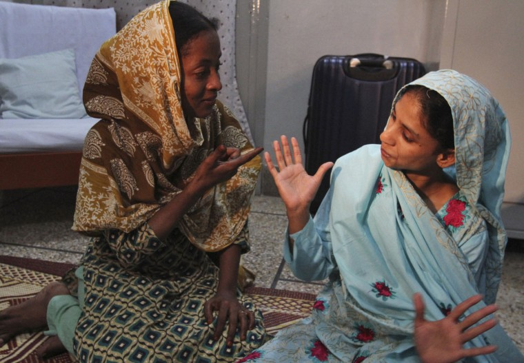 Indian national Geeta, right, who is deaf and mute, communicates with her colleague at charitable Edhi Foundation in Karachi, Pakistan, Thursday, Oct. 15, 2015. Geeta, who accidentally crossed the border into Pakistan as a child nearly 12 years ago will return home soon, an Indian official said Thursday. (AP Photo/Fareed Khan)