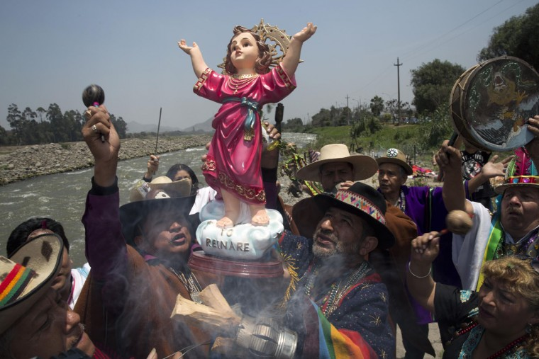 "Shamans hold up a statue of baby Jesus, or ""El Nino"" in Spanish, as they play drums and maracas during a ritual asking for protection from the natural phenomenon known as El Nino, on the outskirts of Lima, Peru, Thursday, Oct. 1, 2015. Peruvian sailors named the formation El Nino—the (Christ) Child—because it was most noticeable around Christmas. Every few years, the winds shift and the water in the Pacific Ocean gets warmer than usual. That water sloshes back and forth around the equator in the Pacific, interacts with the winds above and then changes weather worldwide. In Peru, they've already declared a pre-emptive emergency to prepare for devastating flooding. (AP Photo/Martin Mejia)"