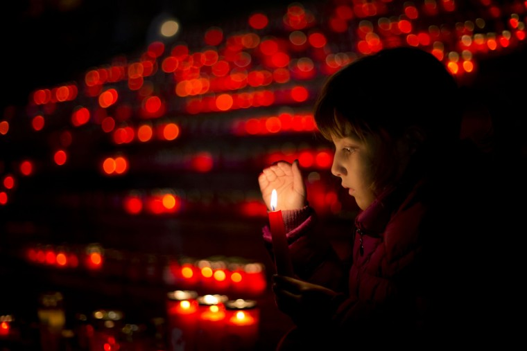 A child sits backdropped by hundreds of lit candles placed on steps during an event marking the international Pregnancy and Infant Loss Remembrance Day in Bucharest, Romania, Thursday night, Oct. 15, 2014. Romania's infant mortality rate is more than double the European Union average, with one in 100 children not reaching their first birthday. (AP Photo/Vadim Ghirda)