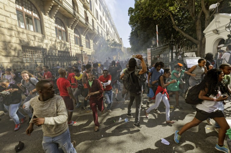 Protesting university students flee as police fire stun grenades outside Parliament in Cape Town, South Africa, Wednesday Oct. 21, 2015. The protests are part of a wave of nationwide protests that have shut down many South Africa universities, which say they are struggling with higher operational costs as well as inadequate state subsidies. (AP Photo)