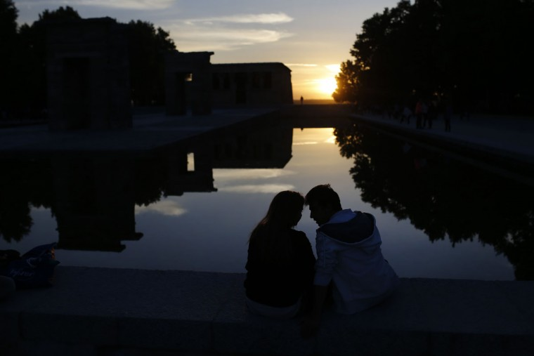 A couple sit by the Temple of Debod as the sun sets in Madrid, Spain, Friday, Oct. 16, 2015. The ancient temple, which was originally built in Egypt, was dismantled and relocated in Madrid as a donation from the Egyptian state to Spain in 1968. (AP Photo/Francisco Seco)