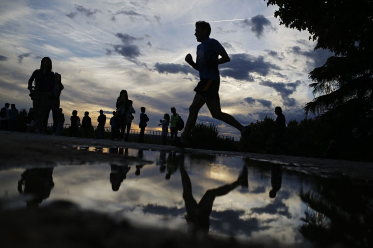 People jog and pause to enjoy the view at the Debod Temple park in Madrid, Spain, Tuesday, Oct. 6, 2015. The park is frequented mostly by locals but also attracts tourists due to its view at sunset. (AP Photo/Francisco Seco)
