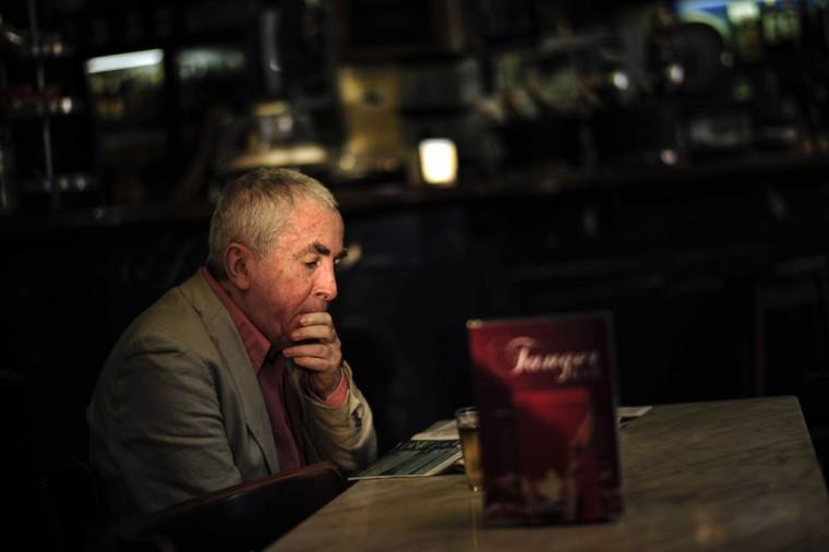 A man reads a newspaper inside of Tanger Bar while the sun set illuminates his face, in San Sebastian, northern Spain, Saturday, Oct. 3, 2015.(AP Photo/Alvaro Barrientos)