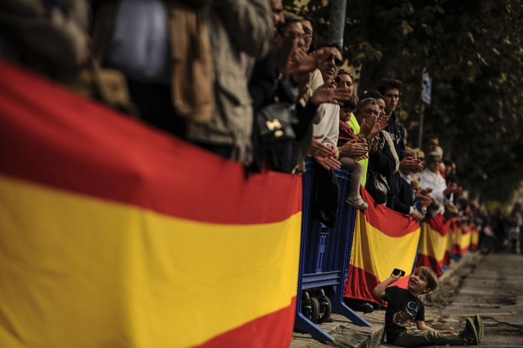 "A young boy, bottom, reacts as he sits beside Spanish flags during an official holiday known as ""Dia de la Hispanidad"" or Spain's Hispanic Day in Pamplona, northern Spain, Monday, Oct. 12, 2015. The Monday holiday commemorates Christopher Columbus' arrival in the New World and is also Spain's armed forces day. (AP Photo/Alvaro Barrientos)"