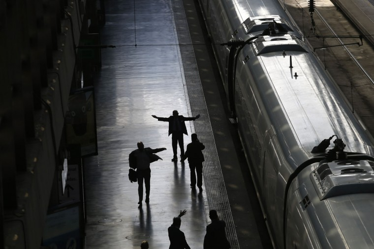 Railway staff supervise the departure of a Barcelona bound high-speed train at the Atocha train station in Madrid, Thursday, Oct. 8, 2015. High-speed train service throughout the northeastern region of Catalonia bordering France was suspended for hours Thursday after thieves stole fiber-optic cable alongside the tracks that officials said was critical for maintaining train safety. (AP Photo/Francisco Seco)