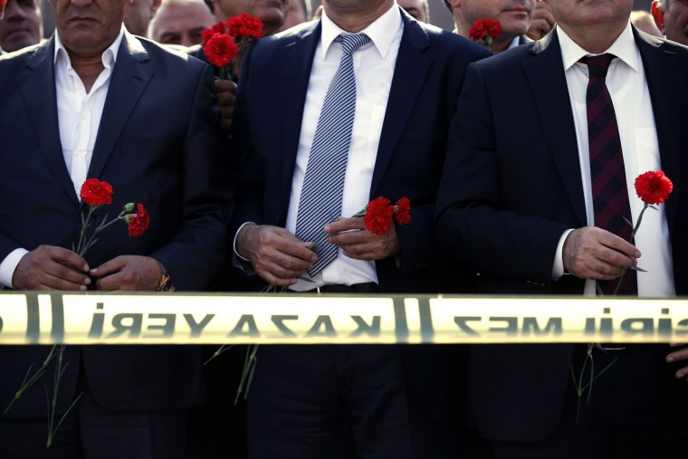 People gather at the site of the two explosions in Ankara, Turkey, to lay flowers for the victims, Tuesday, Oct. 13, 2015. The two suicide bombings in the capital came amid political uncertainty in the country — just weeks before Turkey's Nov. 1 election. (AP Photo/Emrah Gurel)