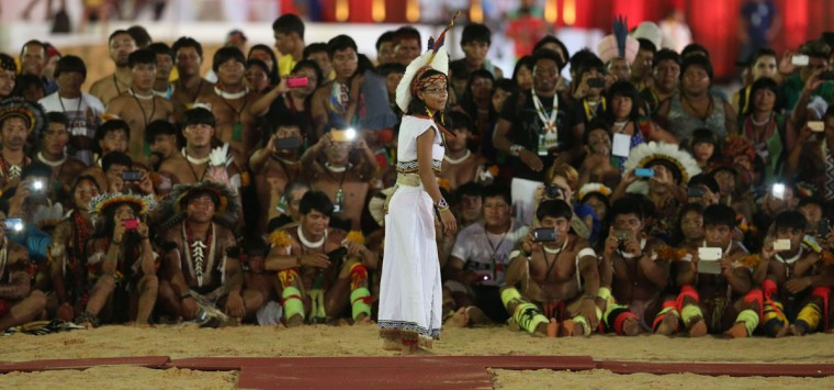 """In this Oct. 24, 2015 photo, indigenous men take photos of a Pataxo indigenous woman from Brazil during a """"parade of indigenous beauty"""" at the World Indigenous Games in Palmas, Brazil. (AP Photo/Eraldo Peres)"""