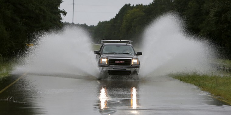 Traffic makes its way through flood waters on Highway 17 North near Awendaw, S.C., Sunday, Oct. 4, 2015. Several sections of Highway 17 are shut down between Charleston and Georgetown. (AP Photo/Mic Smith)
