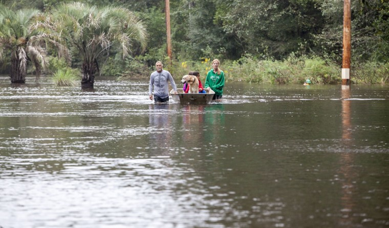 Jerry Hardy and wife his Tracey evacuate their family from flood waters on Waccamaw Drive near Conway, S.C., on Monday, Oct. 5, 2015. As the showers tapered off Monday, the governor warned communities downstream, near the low-lying coast, that they may still see rising water and to be prepared for more evacuations. (Jason Lee/The Sun News via AP)