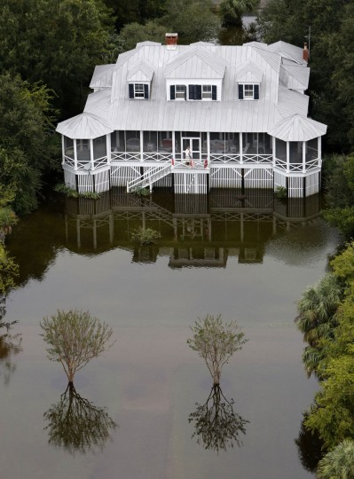 A man talks on his phone on his porch in floodwaters on Sullivan's Island, S.C., Monday, Oct. 5, 2015. The Charleston and surrounding areas are still struggling with flood waters due to a slow moving storm system. (AP Photo/Mic Smith)