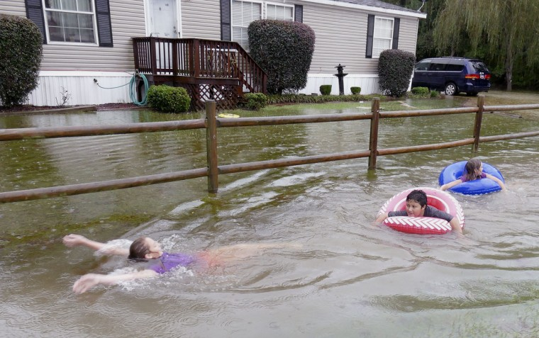 Children play in the flood waters outside of Conway, S.C., Sunday, Oct. 4, 2015. Hundreds were rescued from fast-moving floodwaters Sunday in South Carolina as days of driving rain hit a dangerous crescendo that buckled buildings and roads, closed a major East Coast interstate route and threatened the drinking water supply for the capital city. (Janet Blackmon Morgan/The Sun News via AP)