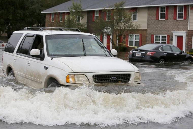 A vehicle pushes flood waters in front of Winyah Apartments in Georgetown, S.C., Sunday, Oct. 4, 2015. Much of South Carolina has experienced historic rain totals coupled with an unusually high lunar tide causing wide spread flooding. The apartment complex has been evacuated. (AP Photo/Mic Smith)