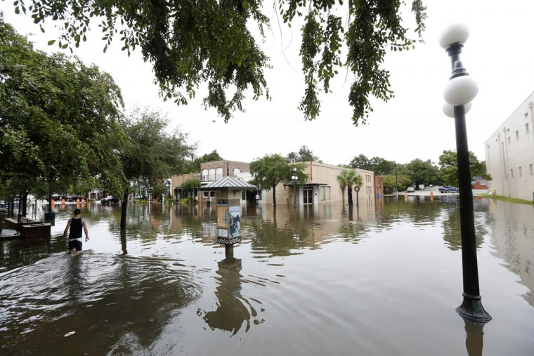 Chris Joseph, far left, inspects the flood waters near high tide in the historic downtown in Georgetown, S.C., Sunday, Oct. 4, 2015. Much of South Carolina has experienced historic rain totals coupled with an unusually high lunar tide causing wide spread flooding. (AP Photo/Mic Smith)