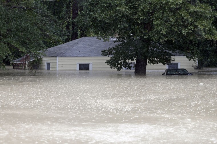 Flood waters engulf a home in Columbia, S.C., Sunday, Oct. 4, 2015. The rainstorm drenching the U.S. East Coast brought more misery Sunday to South Carolina, cutting power to thousands, forcing hundreds of water rescues and closing many roads because of floodwaters. (AP Photo/Chuck Burton)