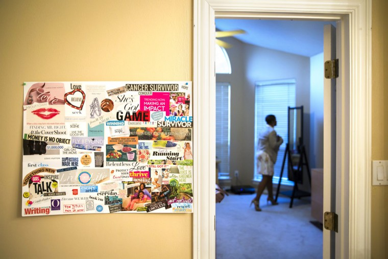 """Breast cancer survivor Noelle LeVeaux prepares to leave the house, in Plano, Texas. A friend encouraged LeVeaux to make a """"vision board"""" when she was diagnosed with breast cancer. The poster board, pasted with inspirational messages cut from magazines, hangs on the wall of the bathroom where LeVeaux gets ready for work. (Smiley N. Pool/The Dallas Morning News)"""