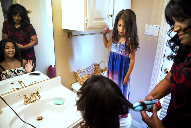 Before leaving for church, Noelle LeVeaux styles hair for her daughter Sydney as her youngest daughter, Jordan, looks on, in Plano, Texas. LeVeaux says cancer taught her to appreciate the girls more and stop projecting her insecurities on them. (Smiley N. Pool/The Dallas Morning News)