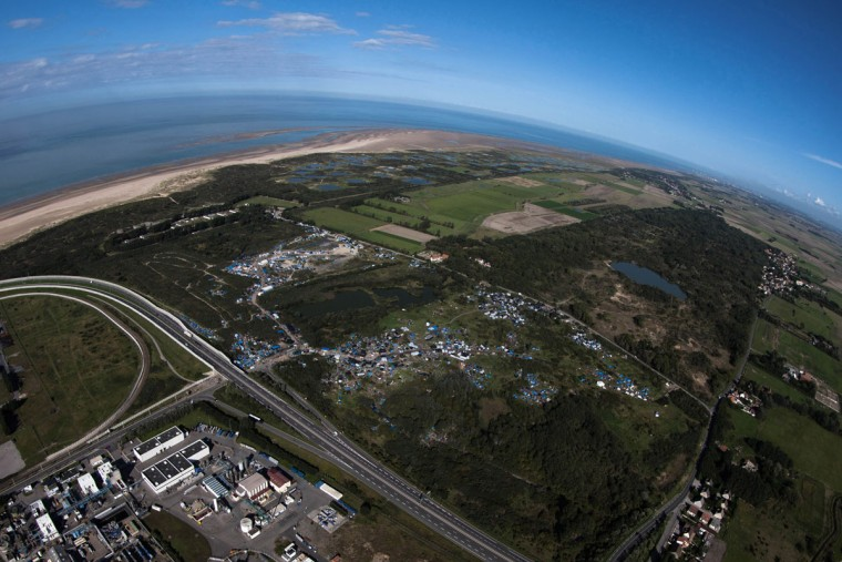 An aerial view of the migrant camp known as the New Jungle Camp, near to Calais, northern France, Friday, Sept. 25, 2015, with the English Channel in background. There are more than 3000 migrants fleeing conflict zones or poverty, according to local officials, at the rapidly growing new Jungle camp outside Calais, hoping to make it across the English Channel to Britain. (AP Photo/Michel Spingler)
