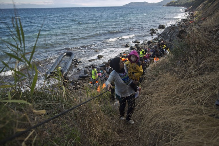 A Syrian refugee woman holding a child climbs a hill using a rope from Volunteers after arriving on a dinghy from the Turkish coast to the northeastern Greek island of Lesbos, Thursday, Oct. 1, 2015. The International Organization for Migration says a record number of people have crossed the Mediterranean into Europe this year. (AP Photo/Muhammed Muheisen)