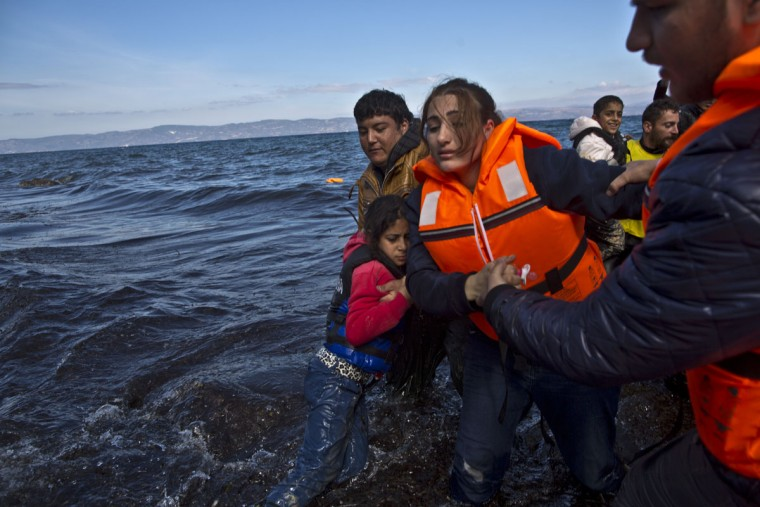 A Syrian refugee woman and a girl make their way out of the water after as they arrive on a dinghy from the Turkish coast to the northeastern Greek island of Lesbos, Thursday, Oct. 1, 2015. The International Organization for Migration says a record number of people have crossed the Mediterranean into Europe this year, now topping a half a million as some 388,000 have entered via Greece. (AP Photo/Muhammed Muheisen)