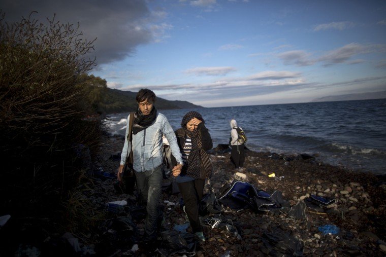 An Afghan refugee couple walk toward the main street after arriving on a dinghy from the Turkish coast to the northeastern Greek island of Lesbos, Thursday, Oct. 1, 2015. The International Organization for Migration says a record number of people have crossed the Mediterranean into Europe this year, now topping a half a million as some 388,000 have entered via Greece. (AP Photo/Muhammed Muheisen)