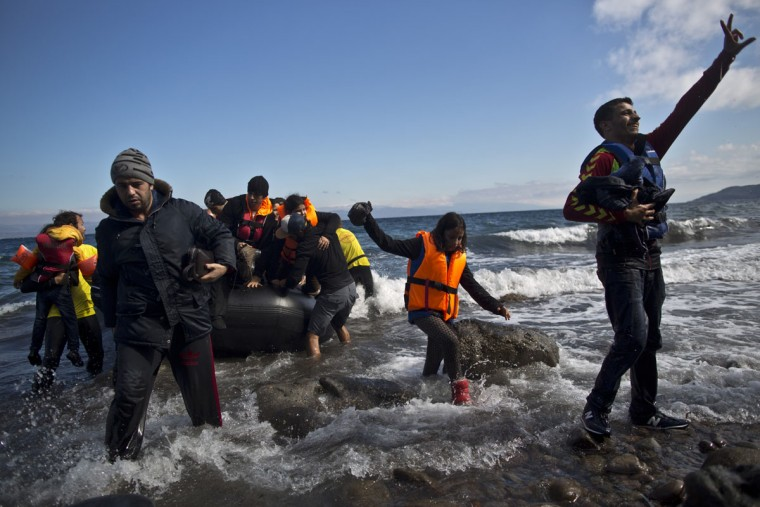 A Syrian refugee, right, gestures as he arrives on a dinghy from the Turkish coast to the northeastern Greek island of Lesbos, Thursday, Oct. 1, 2015. The International Organization for Migration says a record number of people have crossed the Mediterranean into Europe this year, now topping a half a million as some 388,000 have entered via Greece. (AP Photo/Muhammed Muheisen)
