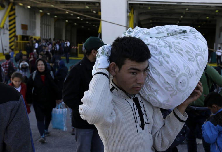 Migrants and refugees arrive on a ferry from the Greek island of Lesbos at the Athens' port of Piraeus, Thursday, Oct. 1, 2015. The Greek ferry Eleftherios Venizelos is part of special ferry service for refugees and migrants that carries 2,500 paying passengers. The International Organization for Migration says a record number of people have crossed the Mediterranean into Europe this year, now topping a half a million as some 388,000 have entered via Greece. (AP Photo/Thanassis Stavrakis)