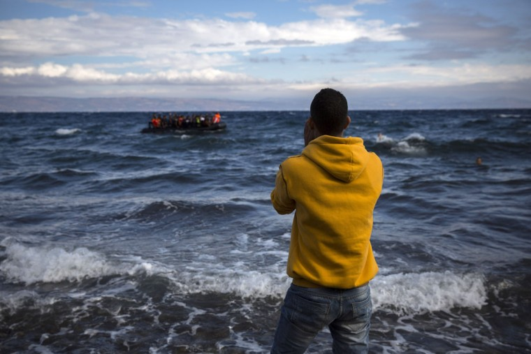 A volunteer gives directions to migrants arriving on a dinghy from the Turkish coast to the northeastern Greek island of Lesbos, Wednesday, Sept. 30, 2015. Authorities in Greece say 2 people have died and 47 people have been rescued from a dinghy near the island on Wednesday. Lesbos is the busiest entry point for migrants reaching the European Union, with some 2,000 arrivals per day from nearby Turkey. (AP Photo/Santi Palacios)