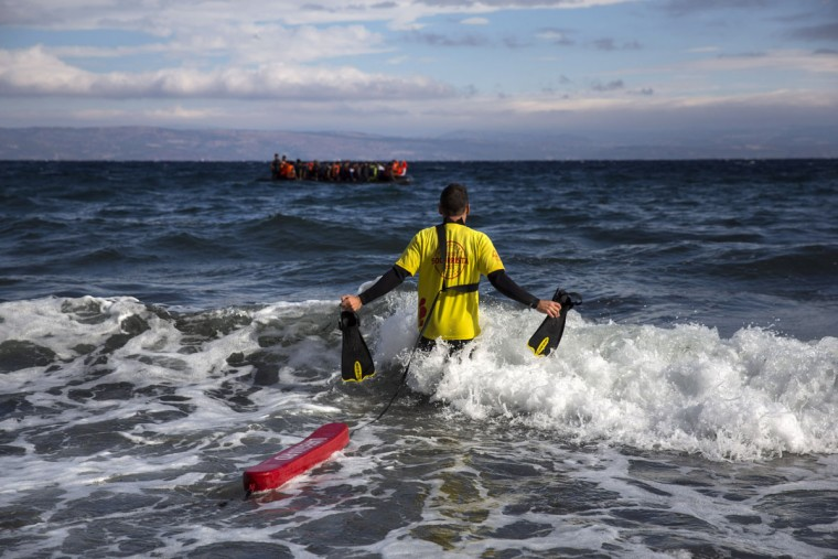 A lifeguard from Barcelona, Spain, working as volunteer enter the water to help migrants and refugees disembark from dinghy's arriving from the Turkish coast to the northeastern Greek island of Lesbos, Wednesday, Sept. 30, 2015. Authorities in Greece say 2 people have died and 47 people have been rescued from a dinghy near the island on Wednesday. Lesbos is the busiest entry point for migrants reaching the European Union, with some 2,000 arrivals per day from nearby Turkey. (AP Photo/Santi Palacios)