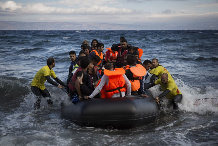 Four lifeguards from Barcelona, Spain, working as volunteers, help disembarking a dinghy as migrants and refugees arrive from the Turkish coasts to the northeastern Greek island of Lesbos, on Wednesday, Sept. 30, 2015. The International Organization for Migration says a record number of people have crossed the Mediterranean into Europe this year, now topping a half a million, with some 388,000 entering via Greece. (AP Photo/Santi Palacios)